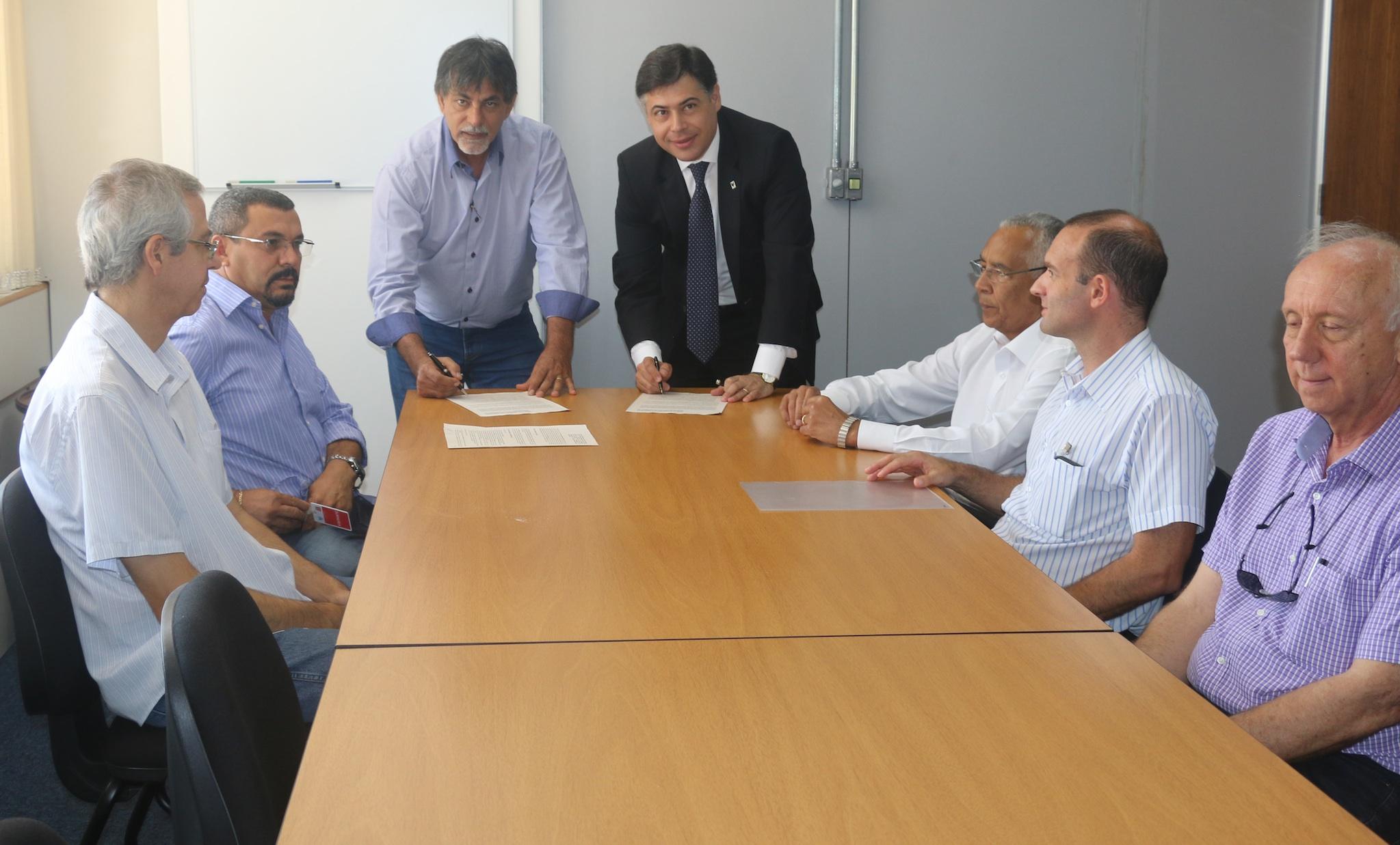 Norival, à esquerda, e Carlos Roberto, à direita, assinam convênio.